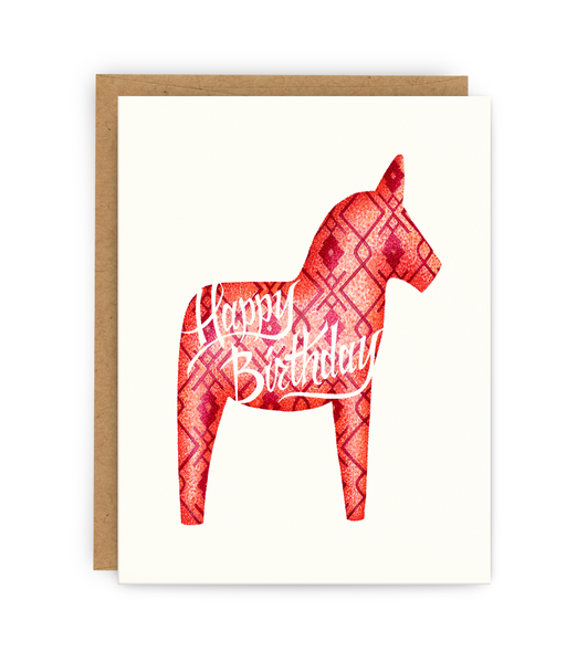 birthday greeting card and kraft envelope featuring pink dala horse and typography