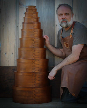 Robert LeHay with a stack of boxes handcrafted by LeHay's Shaker Boxes, Embden, Maine