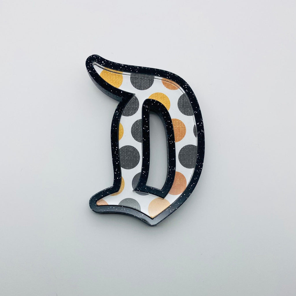 "Flare Printed Gothic ""D"" Brooch in Black Glitter with Orange Polka Dot Print"