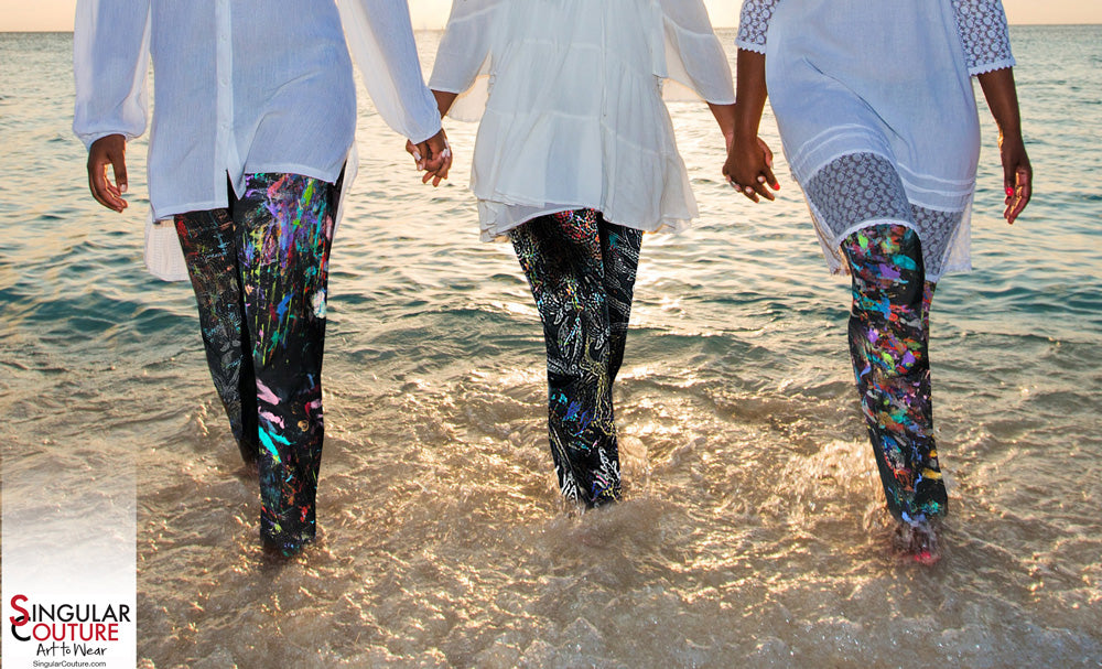 three ladies wearing painted jeans in the ocean