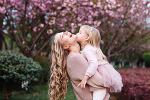 Mother laughing with child in her arms giving her a kiss