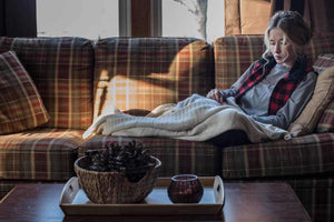 Woman sitting on the couch with a blanket