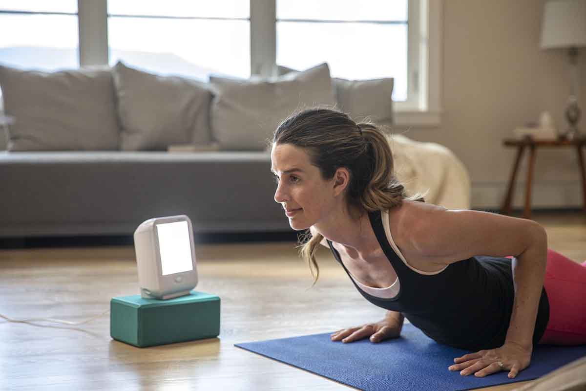 Woman doing yoga pose next to happylight compact