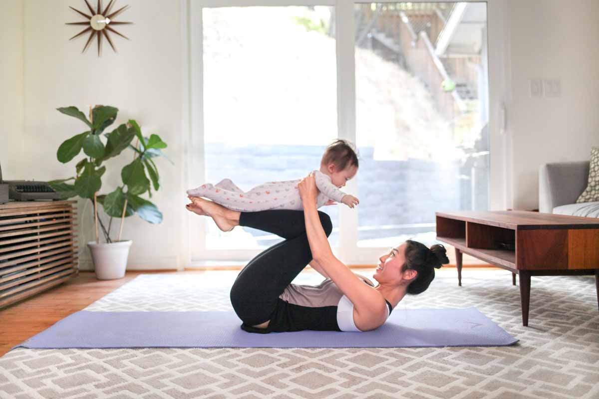 Woman doing yoga with her baby