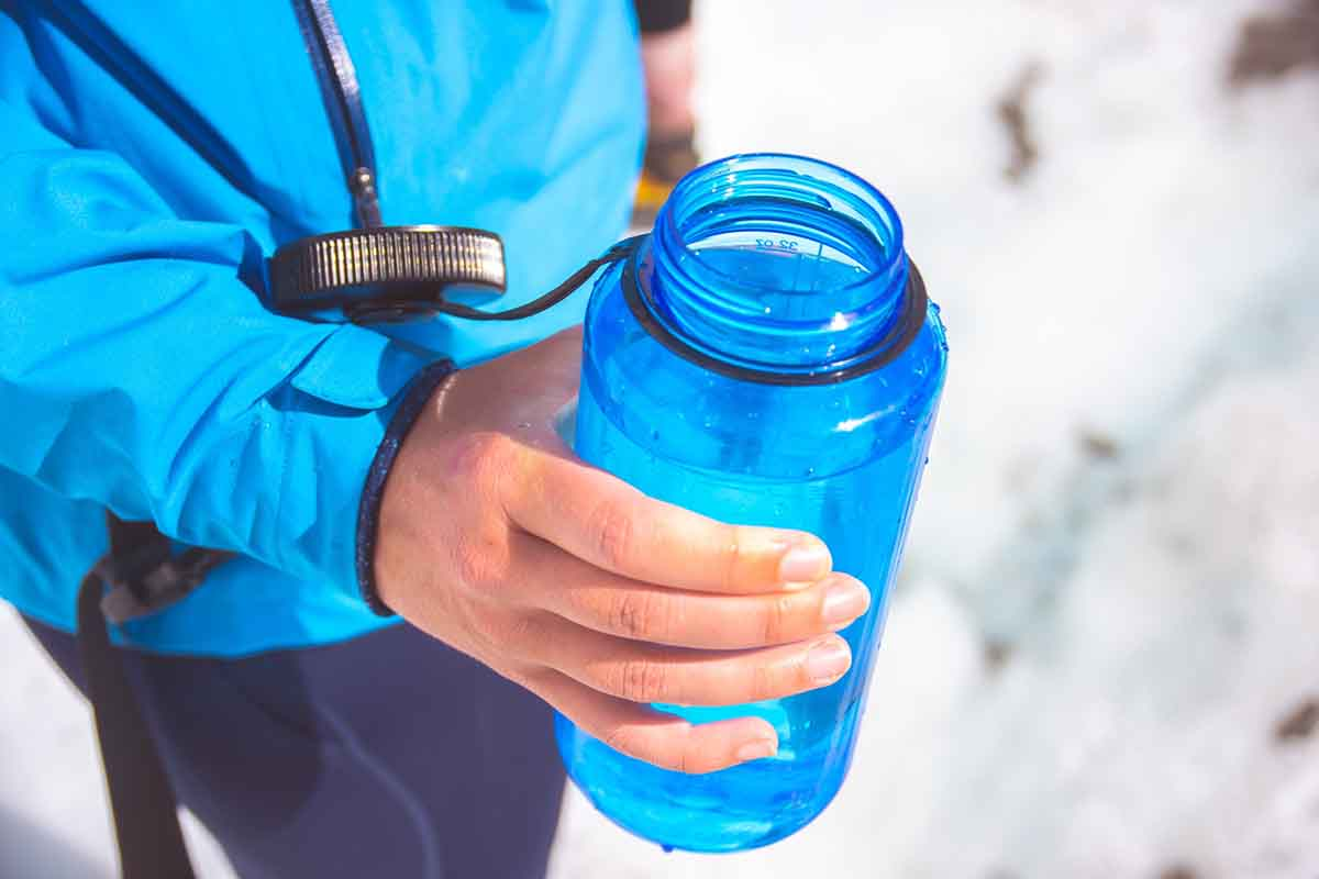 Runner holding blue reusable water bottle
