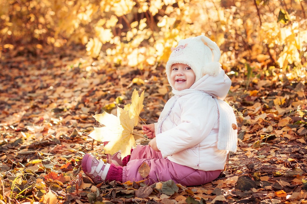 Smiling toddler in fall leaves