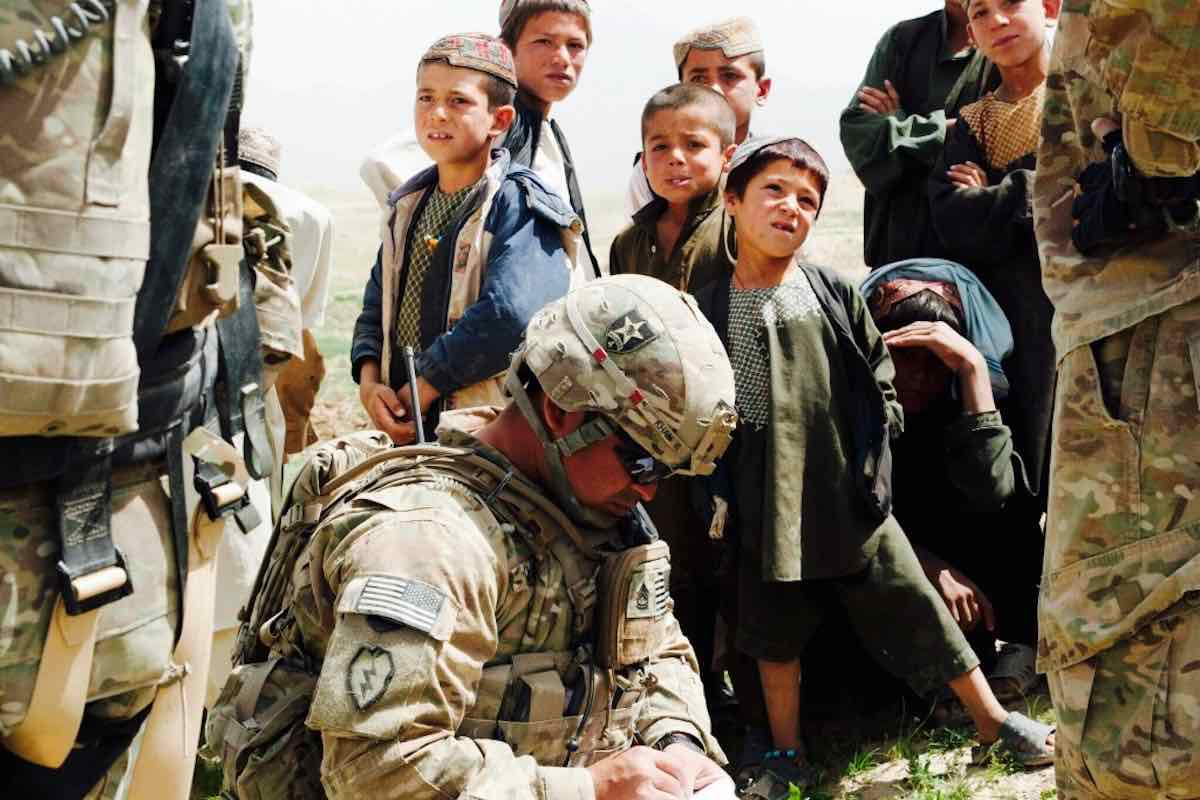 Soldier surrounded by afghan children