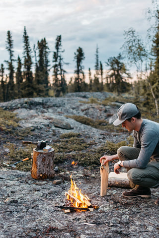 image of man starting a fire in the wilderness