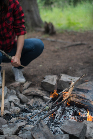 image of a guy starting a small fire using flint and steel