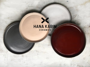 Handmade round ceramic plates in pale pink, deep dark burgundy red, matte grey and matte white, handcrafted by Hana Karim Ceramics