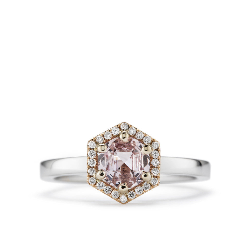 Natural peach sapphire with diamond halo engagement ring.