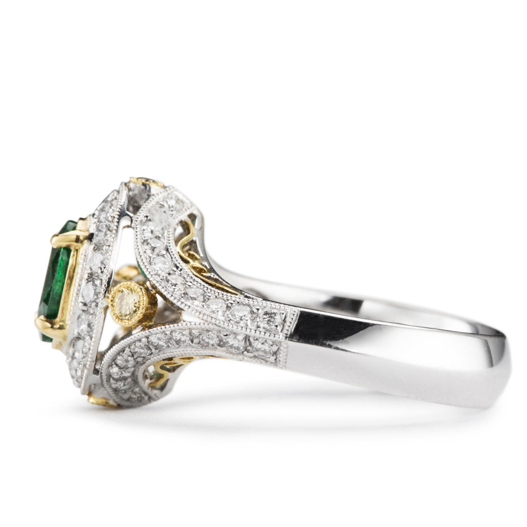 Emerald and diamond ring in white gold with yellow gold diamond accents.