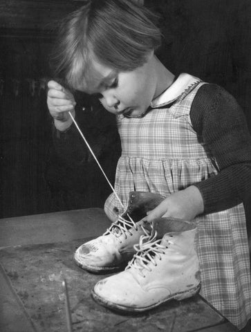 Girl lacing up hi-top shoes