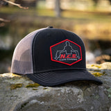 A black/charcoal NCB patch style snapback hat positioned on a rock