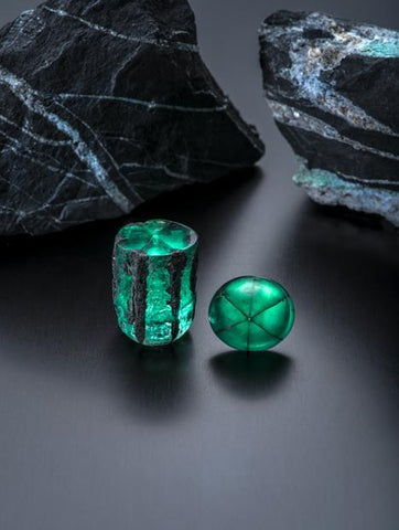Trapiche emeralds from Penas Blancas mine, Colombia. Rough crystal is 58.83 ct; large cabochon is 22.74 ct. The background consists of two carbonaceous shale rocks with quartz, pyrite and the beginnings of emerald formation. Courtesy of Jose Guillermo Ortiz. Photo by Robert Weldon/GIA.