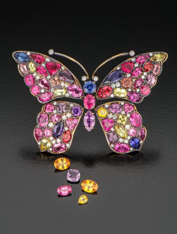 Gold butterfly with Tanzanian sapphires, spinels and garnets, accompanied by loose purple spinel, pink spinel and yellow sapphire. Courtesy of Akiva Gil Co. Photo by Robert Weldon/GIA.