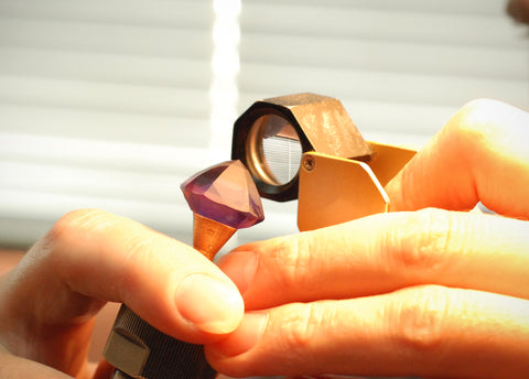 Photo of a gem cutter inspecting the gems before sending it to the polish