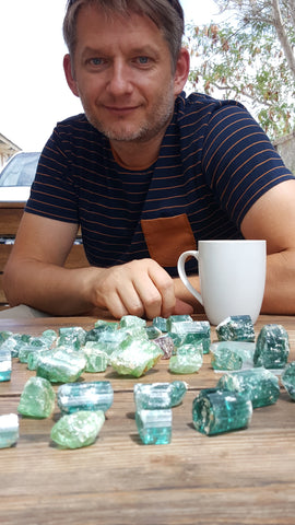 Nomad's Mikola Kukharuk at the morning table staring upon a hefty rough Namibian tourmaline meal