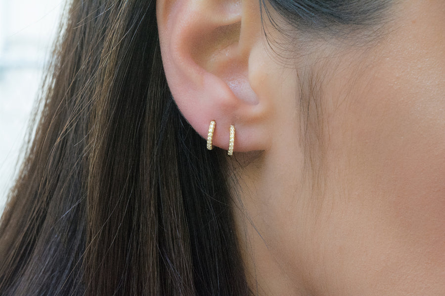 a model wearing two small huggie hoop earrings made of pave cubic zirconia stones