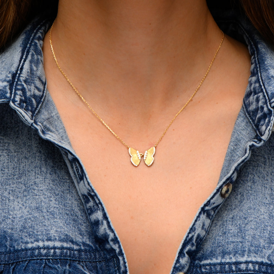 model wearing gold butterfly necklace