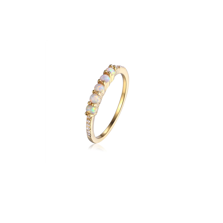 dainty gold opal stacking ring featuring 5 small opal stones set on a thin cubic zirconia pave band
