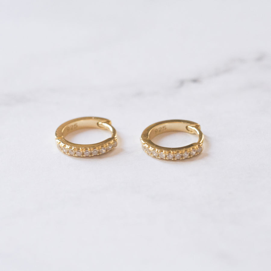 a pair of gold, small hoop earrings, with pave cubic zirconia stones
