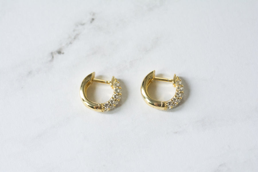a pair of thick and small, gold, huggie style hoop earrings that have cubic zironia stones in front