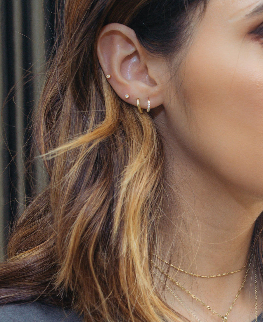 a model wearing a 4 earring styles, two small stud earrings, and two small huggie hoop style earrings, one plain and another one with diamond stones