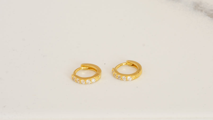 a pair of gold huggie hoop earrings made of cz stones