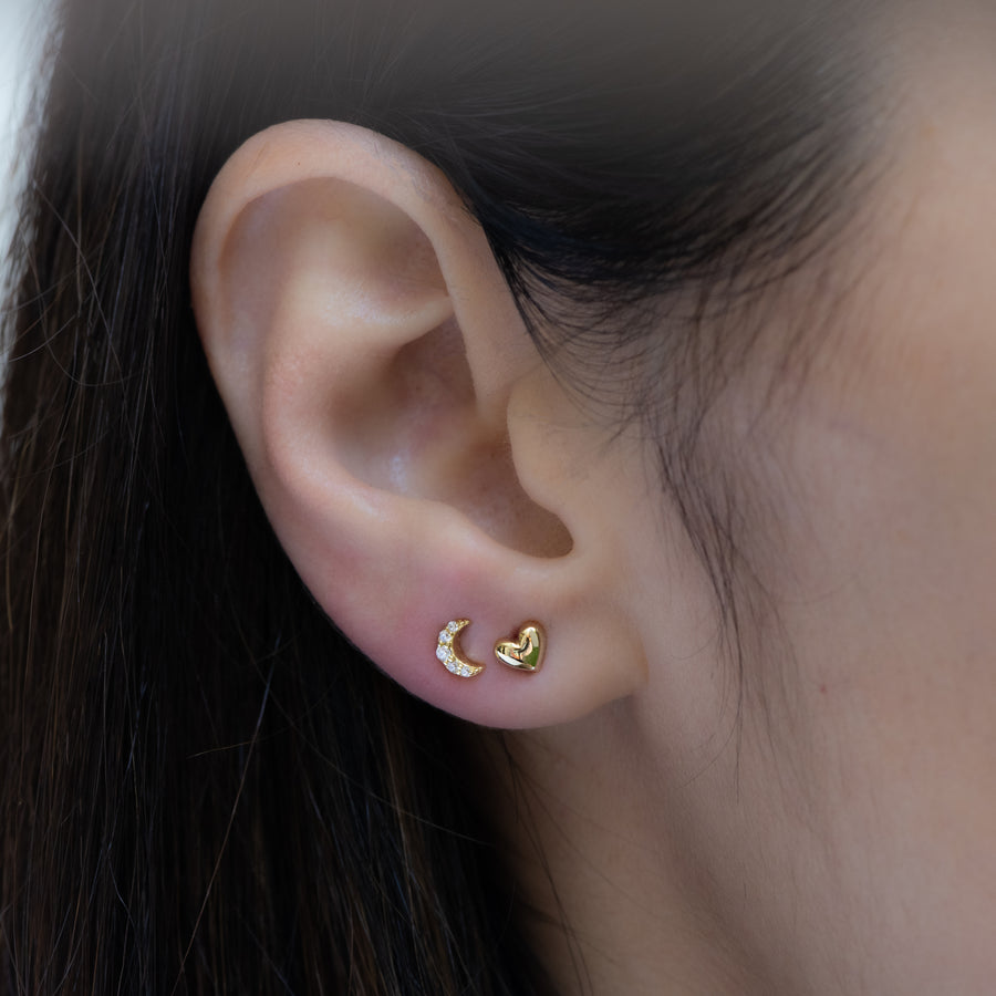gold heart stud earrings paired with a dainty moon stud