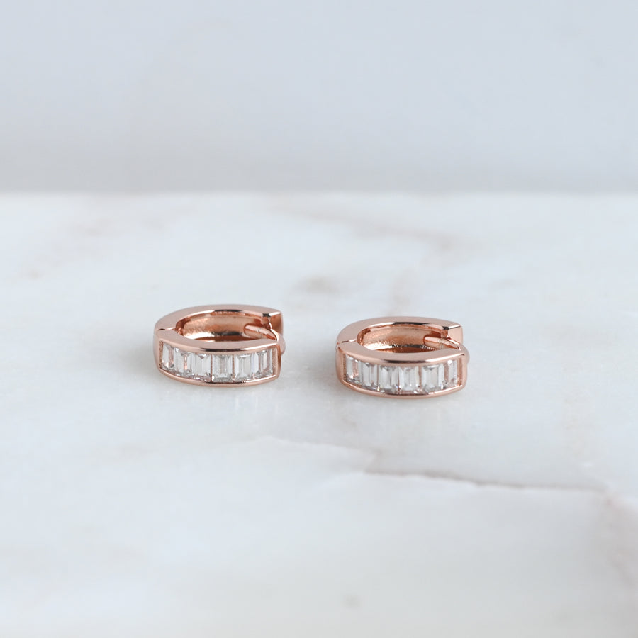 a pair of rose gold baguette studded small hoop earrings