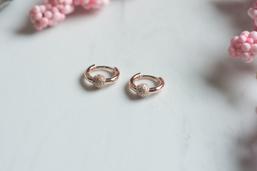 a pair of rose gold huggie hoop earrings