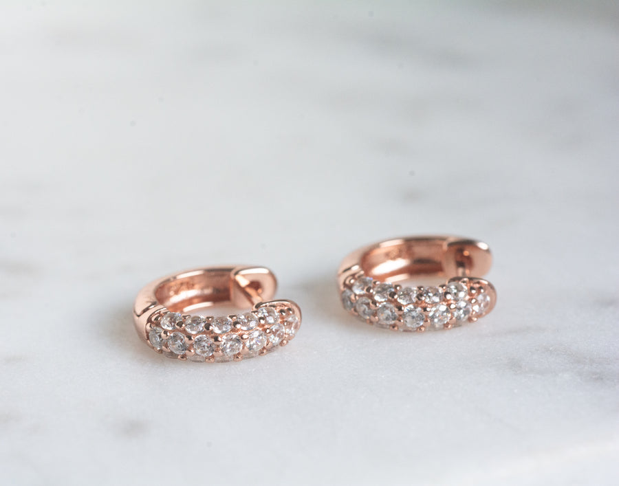 a pair of rose gold small huggie hearings with cubic zirconia stones