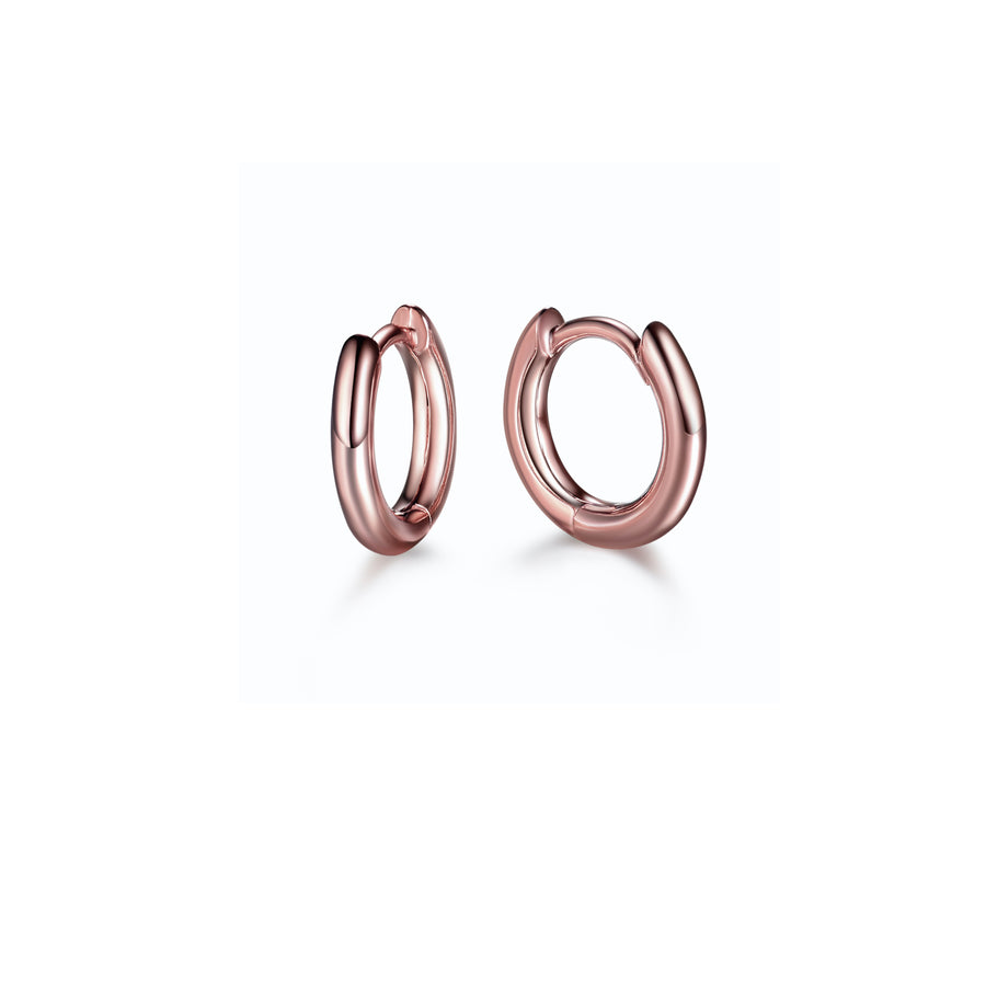 a pair of minimalist rose gold huggie hoop earrings