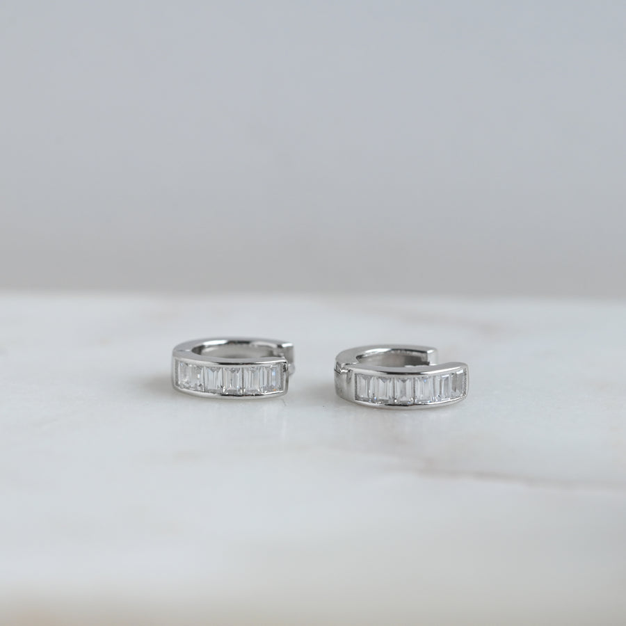 a pair of silver small hoop earring with baguette stones