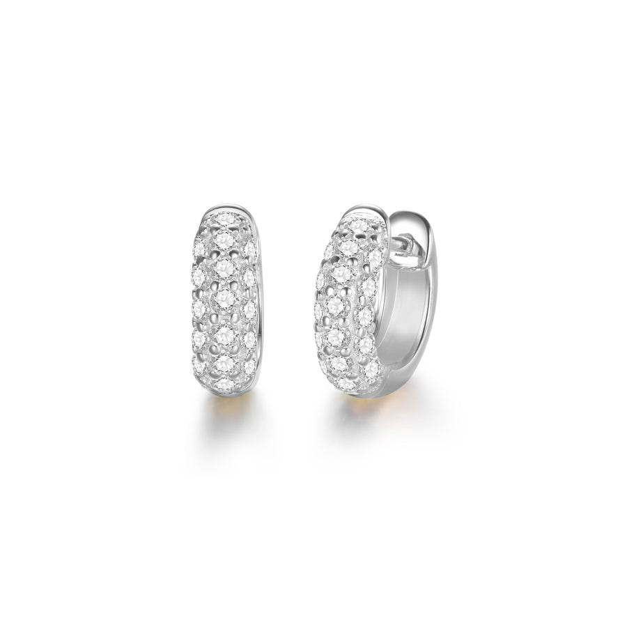a pair of silver, huggie style hoop earrings with diamond stones
