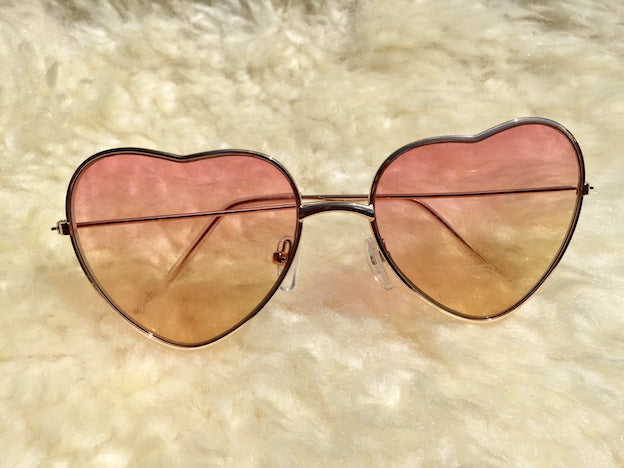 Fall in love with these Take A Piece Of My Heart hippie lovin' shades. Pink yellow ombre lenses with UVA/UVB protection are gentle on your eyes.