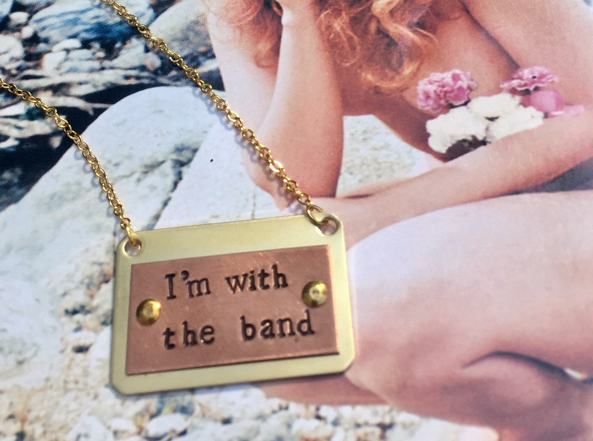 this I'm With The Band necklace is your backstage pass to wherever you want to go. Original design and HAND-STAMPED BY LOCAL LA ARTISTS, THIS NECKLACE IS MADE OF COPPER AND BRASS.