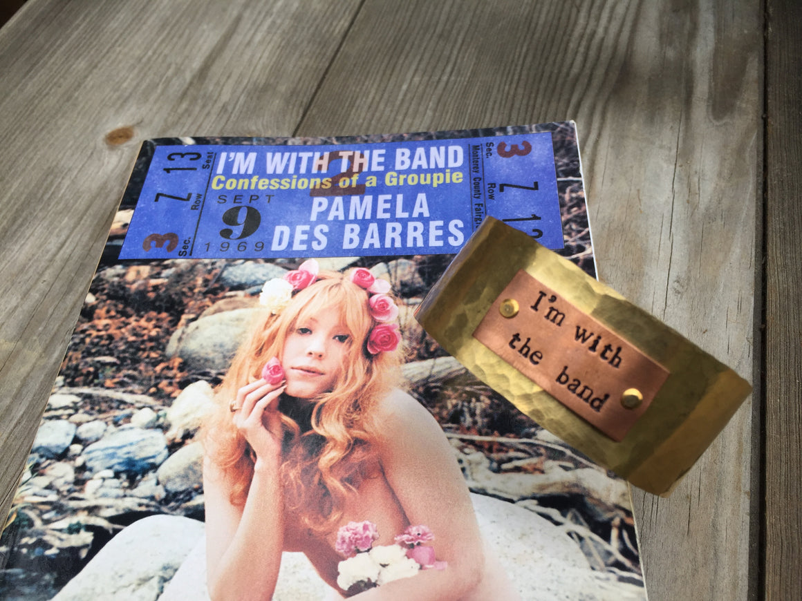 I'm With The Band and I'm lovin' it. This hand-stamped original design in texturized Raw Brass and Aluminum is made in Los Angeles by local artists -  adjustable cuff measures 1″ and is guaranteed to make you smile.