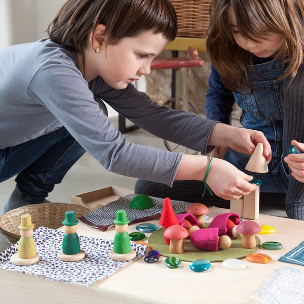 children playing with grapat nins in the woods wooden waldorf toys