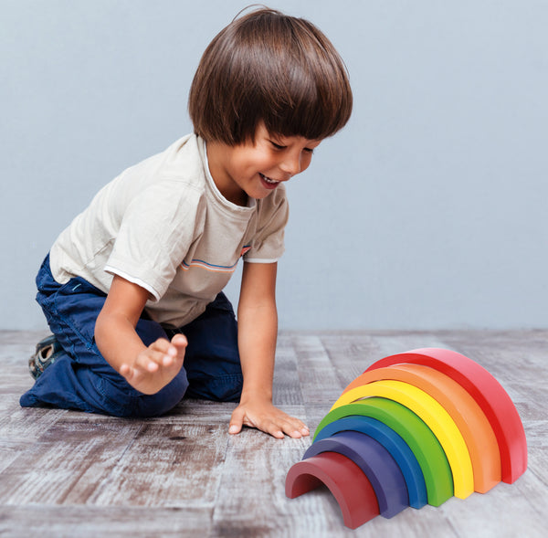 boy playing with Small Foot Rainbow Building Blocks