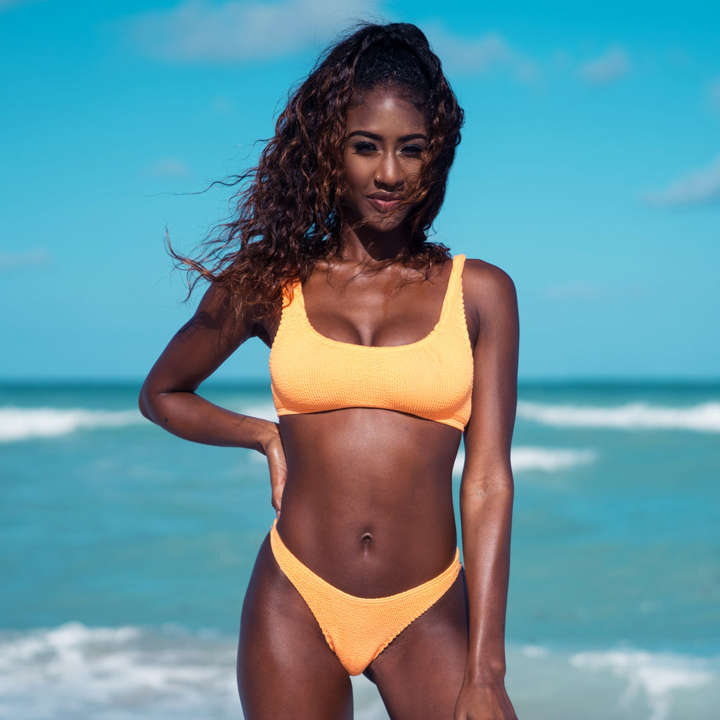 Dark skinned brunette woman in orange bikini on beach