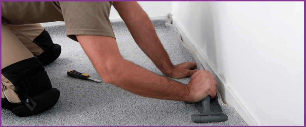 Man fitting carpet with new carpet gripper rods