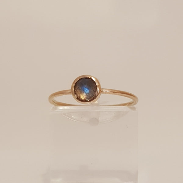 9 ct rose gold ring encasing the labradorite gem stone that protrudes slightly into a soft point.