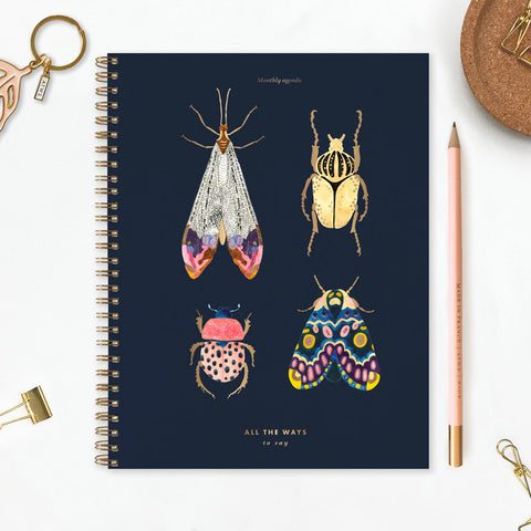 Monthly planner with four jewel like coloured bugs with gold embellishment on a dark grey background.