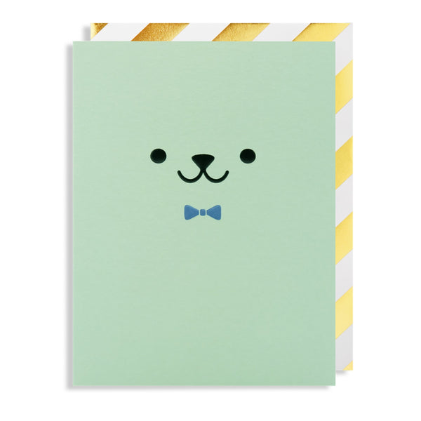 This minty green card has a embossed cute creature face on the front with a bright blue bow tie