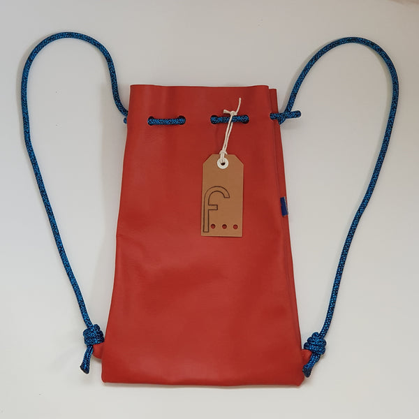This burnt orange leather backpack is super soft and the corresponding cord is bright blue with a black fleck. There is no internal lining.  It has an internal strap with a metal clasp to attach your keys to.
