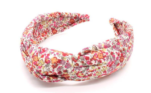 Floral pattern padded headband with twisted fabric knot.