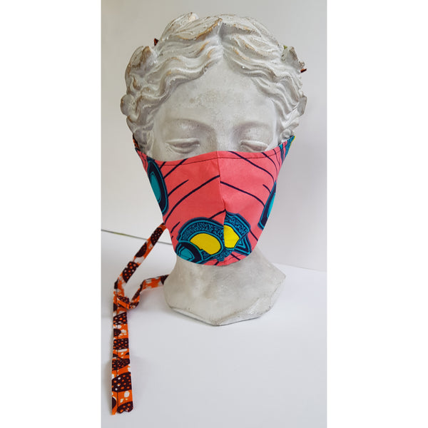 The masks fits across your nose and under your chin.  The main colours and pattern. Pink coral, turquoise, dark blue, yellow.  The pattern has a tear drop shape and lines running diagonally. The lining is black and white and the ties are orange, white and brown.