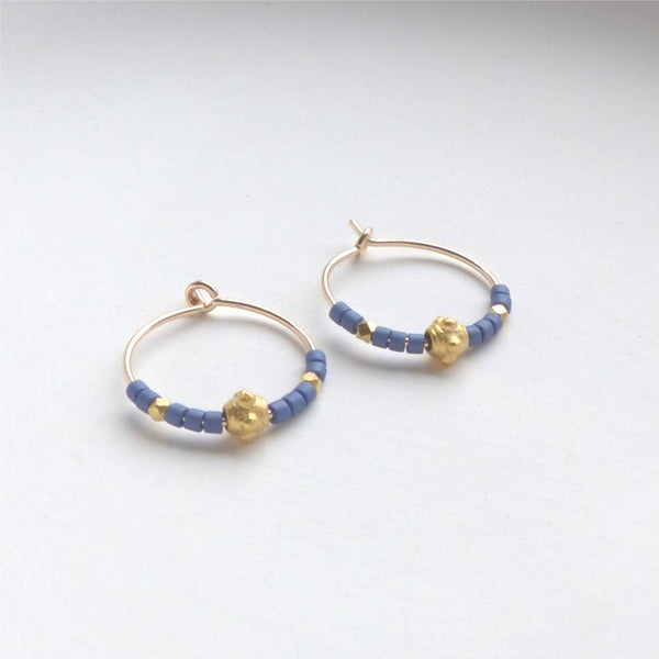 Gold hoop earrings with blue and gold beads.